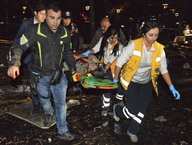 People carry an injured person after an explosion in the busy center of Turkish capital, Ankara, Turkey, Sunday, March 13, 2016. The explosion is believed to have been caused by a car bomb that went off close to bus stops. News reports say the large explosion in the capital has caused several casualties. (Selahattin Sonmez/Hurriyet Daily via AP) TURKEY OUT